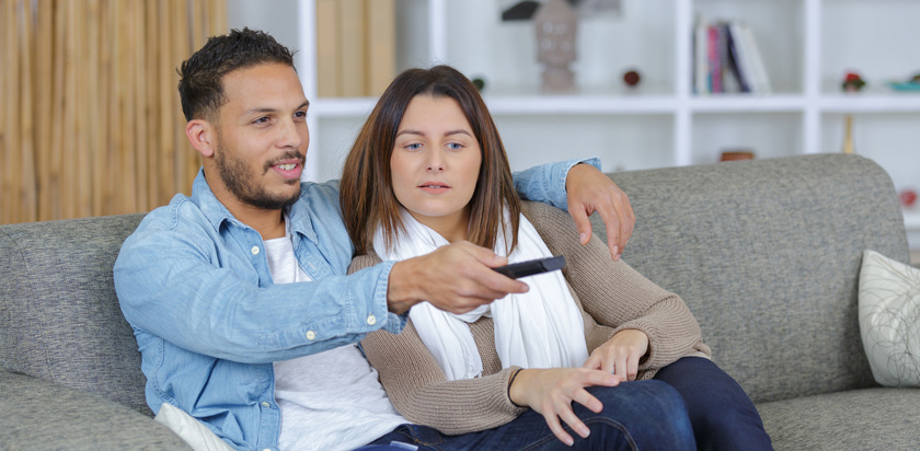 Couple sat on sofa, man holding remote control
