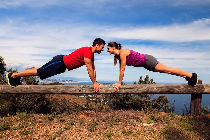 A man and a woman doing push-ups