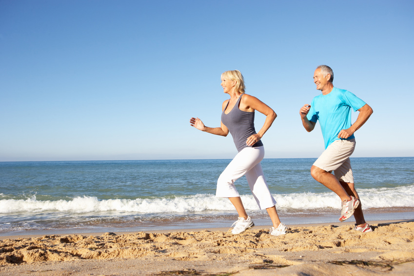 Senior Couple In Fitness Clothing Running Along Beach